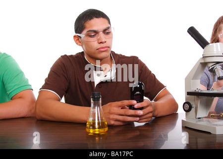 Ein Teen Schüler in der Klasse mit seinem Handy - Stockfoto