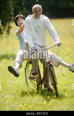 Ältere glückliche Paar auf einem Fahrrad - Stockfoto