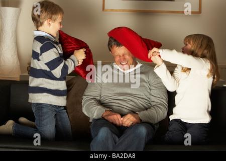 Vater und zwei Kindern In Kissenschlacht - Stockfoto