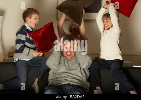 Eltern und zwei Kindern In Kissenschlacht - Stockfoto