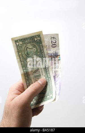 Hand, die eine amerikanische eine Dollarnote und zwanzig Pfund britische Banknoten - Stockfoto