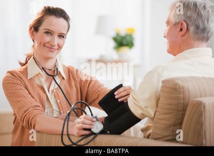 Krankenschwester, die senior woman Blutdruckmessung - Stockfoto