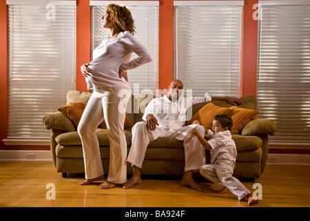 Schwanger afroamerikanische Frau im Wohnzimmer mit Familie - Stockfoto