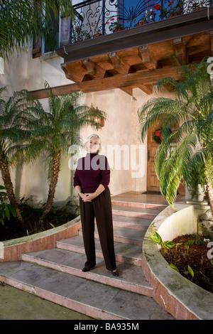 Porträt von senior Frau stand vor luxuriöses Zuhause - Stockfoto