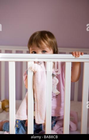 Ein einjähriges Baby Mädchen in ihrem Kinderbett. - Stockfoto