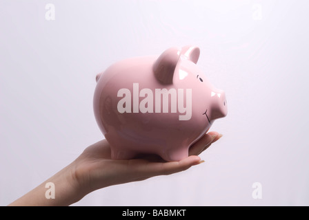 Zarte Frauenhand hält ein rosa Sparschwein - Stockfoto