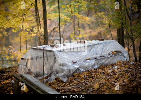 Picknick-Tisch in den Wäldern bedeckt aus Kunststoff zum Schutz - Stockfoto