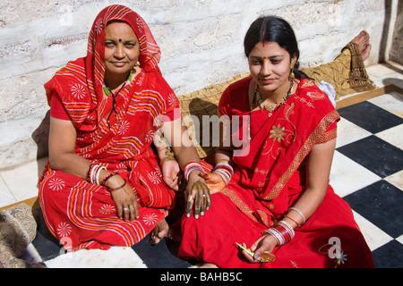 Junge Frau, die Verzierung ihrer Mutter hand, Sachiya Mata Tempel, Osian, in der Nähe von Jodhpur, Rajasthan, Indien - Stockfoto