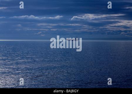 Einsamer Öltanker auf dem Meer in die Straight of Georgia mit ein hoffnungsvolles Licht am Horizont. - Stockfoto
