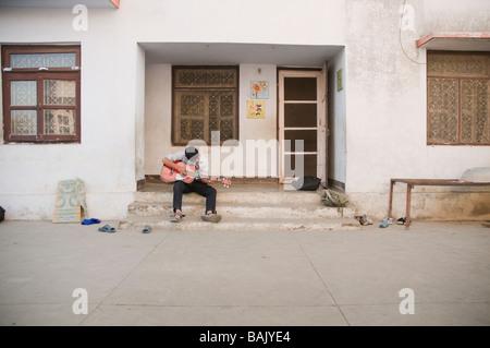 Junge spielt Gitarre vor Haustür - Stockfoto