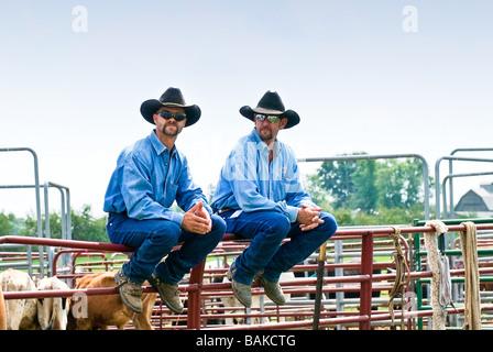 Zwei Cowboys sitzen auf dem Zaun bei einem rodeo - Stockfoto