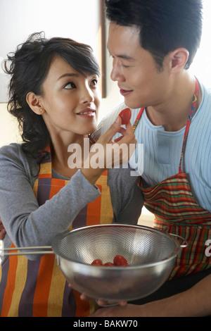 Junges Paar In der Küche Lächeln einander an - Stockfoto