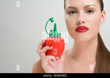 Frau hält eine Flasche Tomaten-ketchup - Stockfoto
