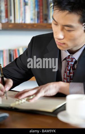 Geschäftsmann Schrift In einem Buch - Stockfoto