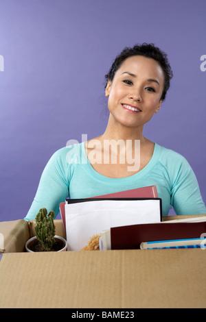Junge Frau Schreibtisch ausräumen - Stockfoto