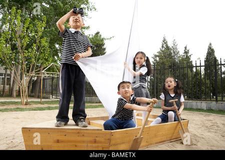 Kleine Kinder sitzen In einem Boot In einem Sandkasten - Stockfoto