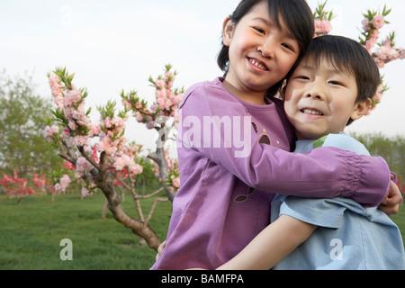 Bruder und Schwester glücklich umarmt im Park - Stockfoto