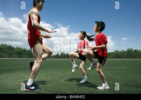 Kinder und Trainer vor Ort ausgeführt - Stockfoto