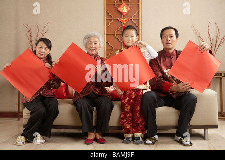 Familie In traditioneller Kleidung Papier hochhalten - Stockfoto