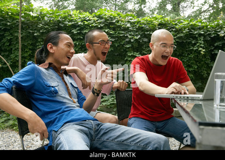 Drei junge Männer jubeln und lachen über Laptop - Stockfoto