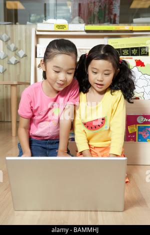 Kleinkinder mit Hilfe eines Computers - Stockfoto