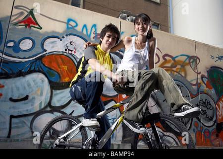 Jugendliche sitzen auf Fahrrad - Stockfoto