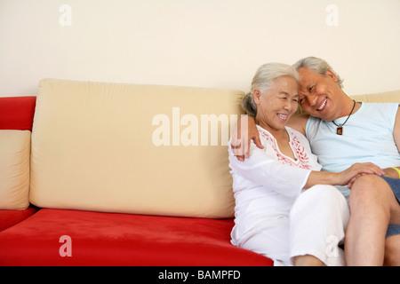 Älteres Ehepaar zusammen auf der Couch sitzen, umarmen - Stockfoto