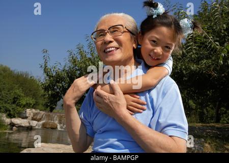 Großvater mit seiner Enkelin Huckepack-Fahrt, - Stockfoto