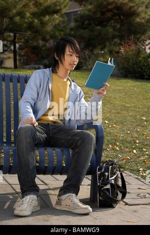 Junger Mann sitzt auf Park Bench Lesebuch - Stockfoto