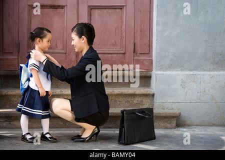 Eine Mutter nimmt ihr Kind zur Schule am Morgen - Stockfoto