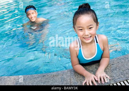 Vater und Tochter am Pool schwimmen - Stockfoto