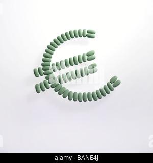 grüne Pillen angelegt in das Euro-Geld-Zeichen-Symbol auf weißem Hintergrund - Stockfoto