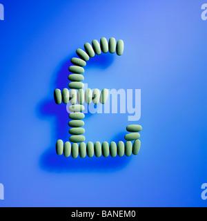 grüne Pillen in den UK Pfund Geldsymbol Zeichen auf blauem Hintergrund angelegt - Stockfoto