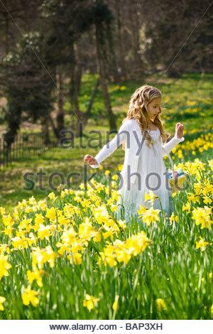 Ein junges Mädchen zu Fuß durch Narzissen mit einem Korb voller Ostereier - Stockfoto