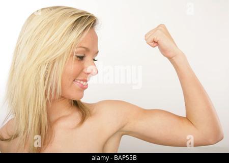 gut durchtrainierten blonden Frau, die die Muskeln auf dem linken ...