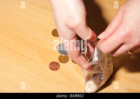 Eine Person zählen Absacken bis kleine ändern und Münzen an die Bank und Börse für größere Geld nehmen auf Kupferplatten - Stockfoto