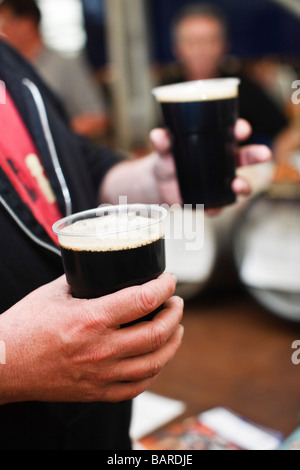 Mann, hält zwei Pints Stout in Kunststoff Pint Gläser - Stockfoto