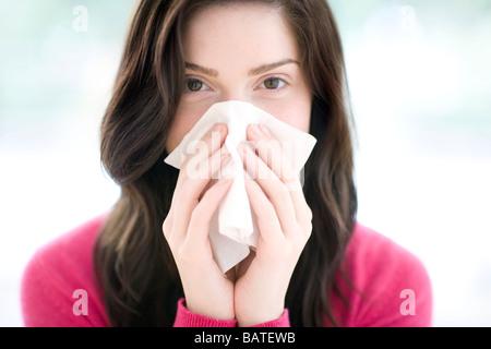 Frau bläst ihre Nase mit Ahandkerchief. Sie ist in ihren Zwanzigern. - Stockfoto
