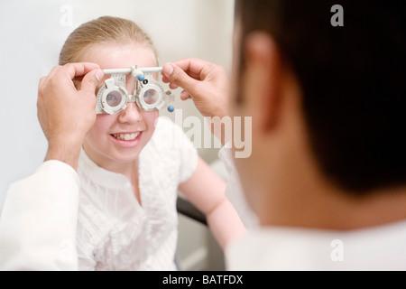 Augenuntersuchung. Optiker mit Vorhofflimmern Rahmen auf ein zehn Jahre altes Mädchen. - Stockfoto