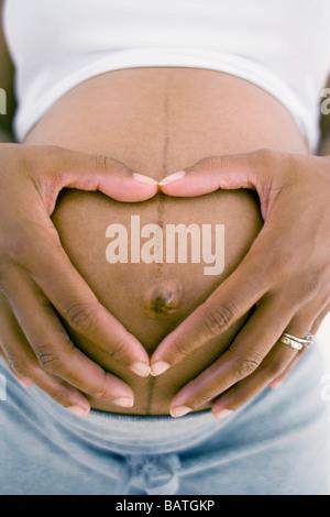 Schwangere Frau bilden eine Liebe Herzform mit ihren Fingern über ihre geschwollenen Bauch. Sie ist auf volle Amtszeit. - Stockfoto