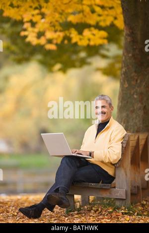 Afrikanischer Mann mit Laptop auf der Parkbank im Herbst - Stockfoto