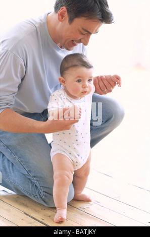 Baby und Vater. 6 Monate altes Baby junge von seinem Vater unterstützt. - Stockfoto