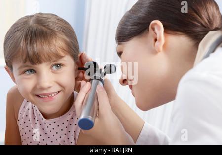 Ohr-Prüfung. Otoskop verwendet wird von einem Arzt für Allgemeinmedizin, um ein sechs-jährigen Mädchen Ohr zu untersuchen. - Stockfoto