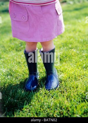 Girl in Stiefeln. Zwei-jährigen Mädchen tragen Wellington Stiefel im Agarden. - Stockfoto