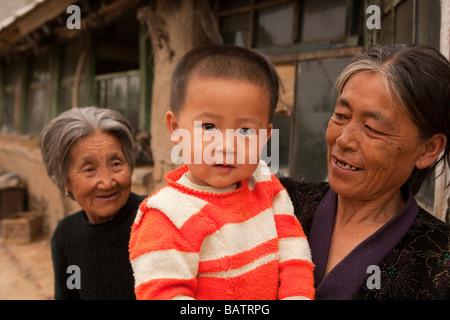 Changchun, Provinz Jilin, China.  Ein kleiner Junge in den Armen seiner Mutter außerhalb der eigenen Wohnung mit - Stockfoto