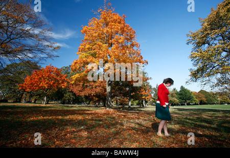 Eine junge Frau trägt einen Rock Spaziergänge durch den Park während der Herbstsaison in Victoria, BC, Kanada. - Stockfoto