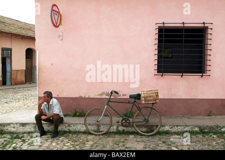 Mann saß an einer Straßenecke neben seinem Fahrrad in Trinidad Kuba - Stockfoto
