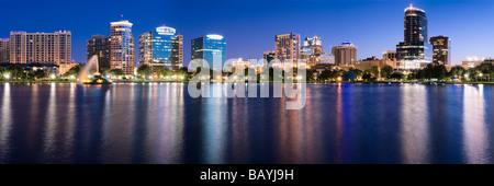 Glühende nächtliche Skyline der Innenstadt von Orlando Florida spiegelt sich in Lake Eola - Stockfoto