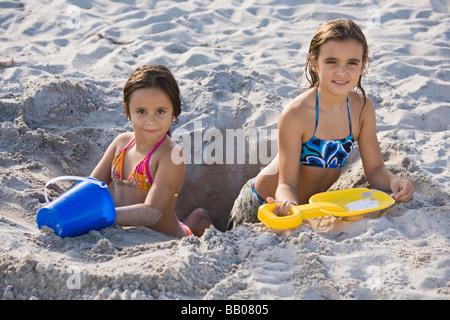 Hispanischen Mädchen Graben im sand - Stockfoto