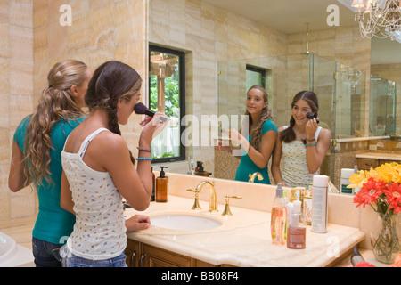 Hispanic Jugendliche beim Schminken im Badezimmerspiegel - Stockfoto